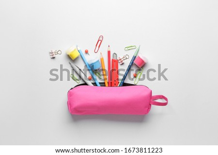 Pencil case and stationery on light background Royalty-Free Stock Photo #1673811223