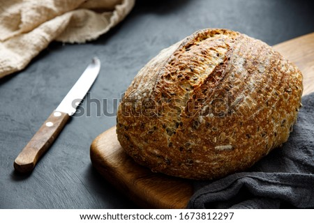 Round loaf of freshly baked sourdough bread with knife on cutting board. Artisan bread with seeds on dark table. Rustic sourdough bread. #1673812297