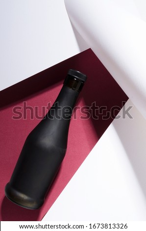 Matte glass bottle of alcoholic drink on the drk red and white surface.Concept of packaging of alcoholic beverages #1673813326