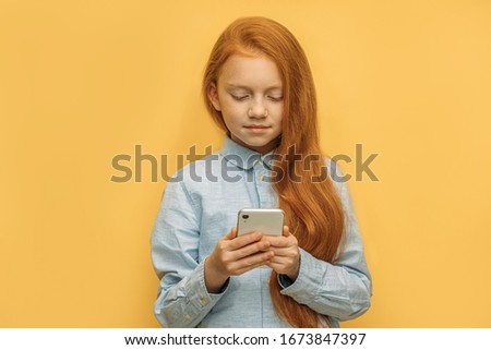 portrait of adorable caucasian red haired girl with mobile phone, pretty kid girl using smartphone, chatting with friend. isolated yellow background. modern technologies concept