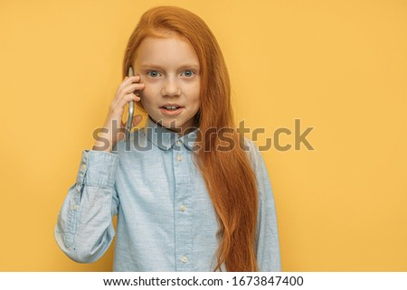 awesome caucasian girl talking on phone with friend, discussing news, school. beautiful child with long red hair and freckles use smartphone isolated over yellow background