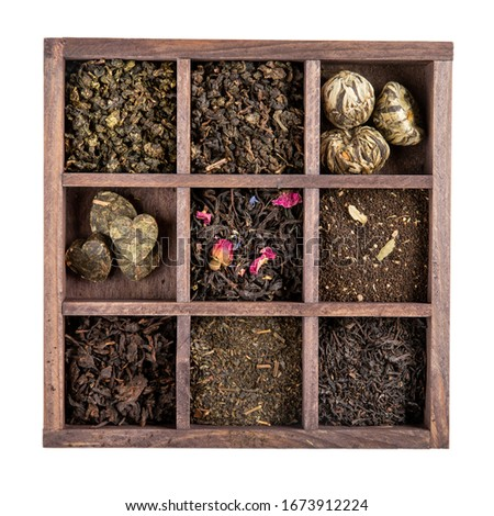 Assortment of dried tea in wooden box isolated on white. Black and green tea collections. Top view.  #1673912224