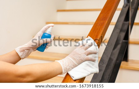 Deep cleaning for Covid-19 disease prevention. alcohol,disinfectant spray on Wipes of Banister in home for safety,infection of Covid-19 virus,contamination,germs,bacteria that are frequently touched . #1673918155