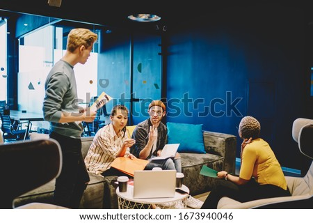 Skilled team of male and female employees sitting together on meeting discussing ideas and plans for cooperation on startup project, professional diverse group of business partners talking together #1673940046