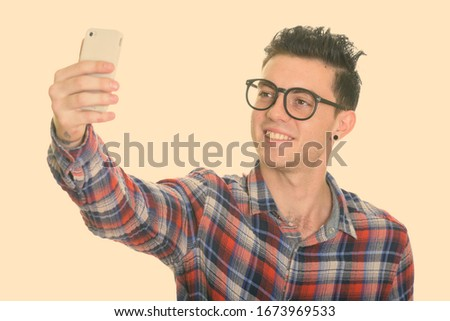 Studio shot of happy young man smiling while taking selfie picture with mobile phone