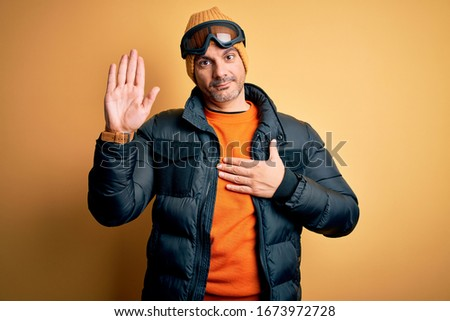 Young handsome skier man skiing wearing snow sportswear using ski goggles Swearing with hand on chest and open palm, making a loyalty promise oath #1673972728