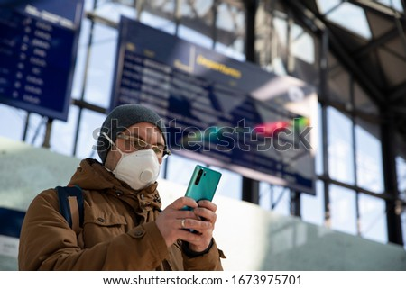 Man in protect mask with mobile phone in public transport while covid19. Coronavirus and people who travel while pandemic. Using phone. #1673975701