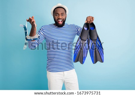 Photo of funny dark skin guy hold diver devices flippers tube goggles mask excited to start sinking wear white sun cap striped sailor shirt shorts isolated blue color background #1673975731