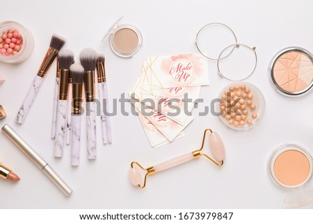 Decorative cosmetics and accessories with business cards of makeup artist on white background