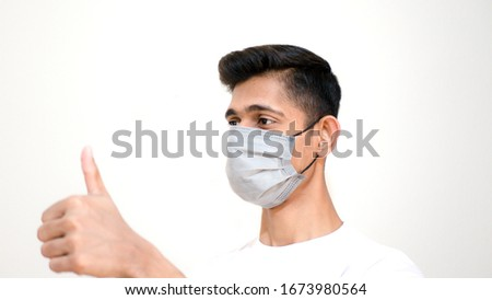 Young Asian boy thumbs up and wearing protective mask against the corona virus covid 19 brown man wearing surgical mask to prevent from virus white background Corona virus pandemic #1673980564