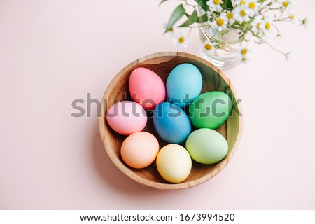 Easter holiday concept. Easter picture, multi-colored eggs in a wooden plate, on a pink background
