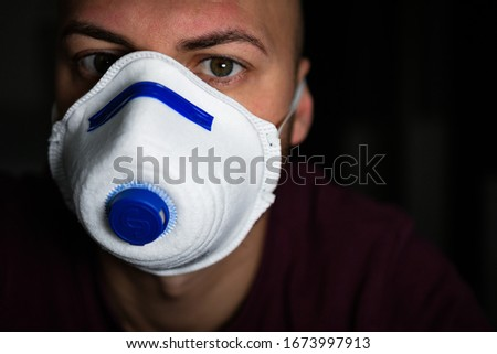 Man with green eyes and with a mask to avoid contagion from the Coronavirus COVID-19 #1673997913