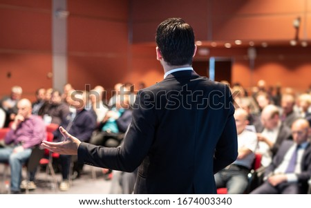 Speaker at Business Conference with Public Presentations. Audience at the conference hall. Entrepreneurship club. Rear view. Panoramic composition. Background blur. #1674003340