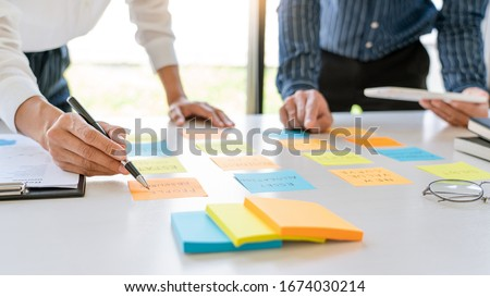 young business workers posting with sticky notes stickers reminders  creative brainstorming at board the colleague in a modern co-working space #1674030214
