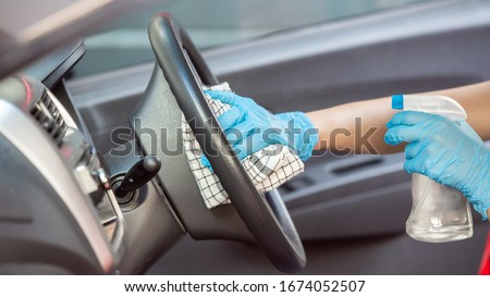 Cleansing car interior and spraying with disinfection liquid. Hands in rubber protective glove disinfecting vihicle inside for protection from virus disease #1674052507
