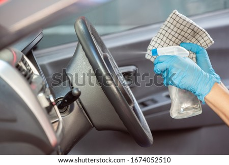 Cleansing car interior and spraying with disinfection liquid. Hands in rubber protective glove disinfecting vihicle inside for protection from virus disease #1674052510