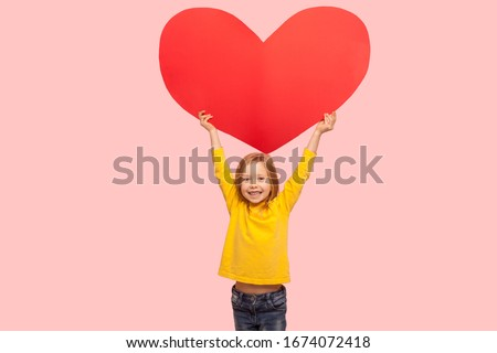 Portrait of sweet cheerful little girl raising large red heart symbol over head and smiling to camera, congratulating on Mother's day, saying I love you. indoor studio shot isolated on pink background