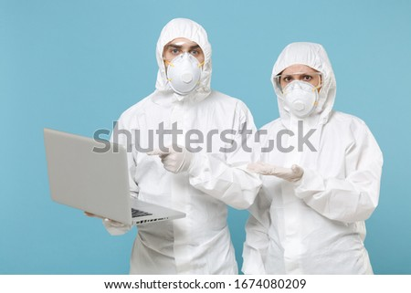 People in protective suits respirator masks hold work on laptop pc computer isolated on blue background studio. Epidemic pandemic new rapidly spreading coronavirus 2019-ncov medicine virus concept #1674080209