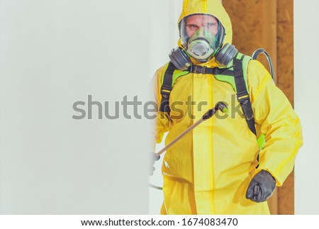 Disinfection For Virus Killing. Worker in Hazmat Suit and Face Protection Mask Spraying  Interior Using Chemical Agents To Stop Spreading Virus Infections. #1674083470