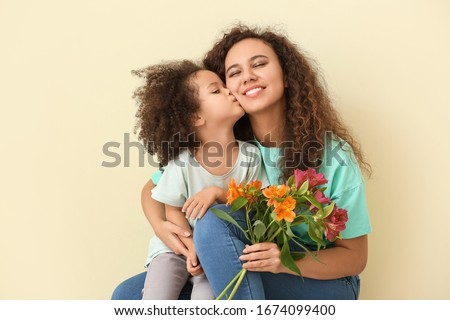 Little African-American girl with her mother and bouquet on color background #1674099400