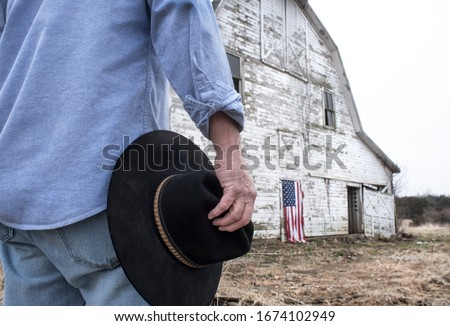 Man holding black cowboy hat standing in front of old barn on farm with American flag hanging on barn door. man's back to camera, cannot see his face. color photo