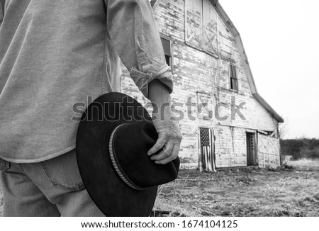 Man holding black cowboy hat standing in front of old barn on farm with American flag hanging on barn door. man's back to camera, cannot see his face. black and white photo