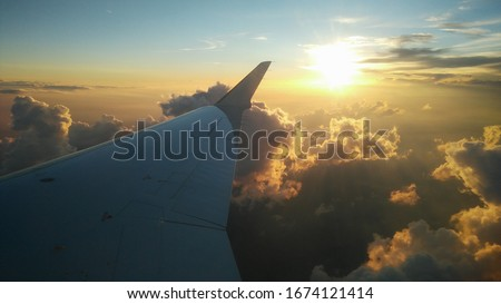 airplane window picture with sun on the horizon