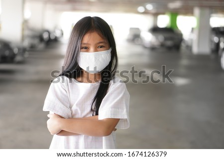 Asian child positive or kid girl smiling wear N95 cloth face mask for close mouth and sick on nose with cold cough and protect PM2.5 dust or influenza virus and bacteria from smoke and crossed arms #1674126379