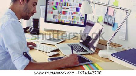 Portrait of young designer sitting at graphic studio in front of laptop and computer while working online.