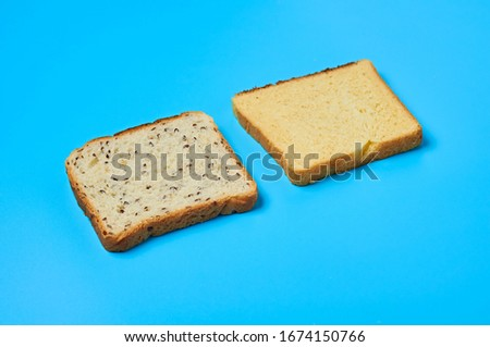 Two square pieces of bread with seeds and vanilla for toast lies on blue table on kitchen. Close-up #1674150766