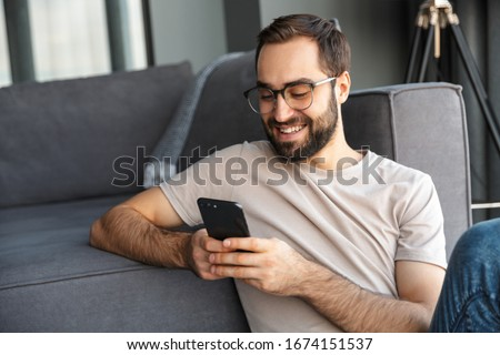 Attractive smart young man sitting on a floor in the living room, using mobile phone #1674151537