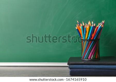 Set of school supplies on table near blackboard #1674165910