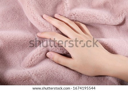 beautiful female's hand on the fabric of plush cloth with soft nap Royalty-Free Stock Photo #1674195544