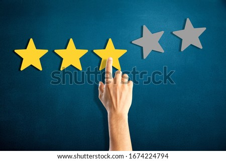 Satisfaction concept. Woman hand giving three star rating #1674224794