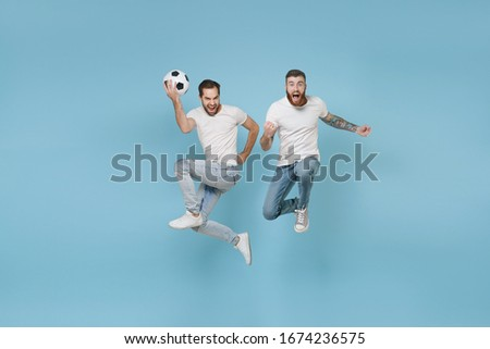 Excited men guys friends in white t-shirt isolated on pastel blue background. Sport leisure lifestyle concept. Cheer up support favorite team with soccer ball, jumping doing winner gesture, screaming #1674236575