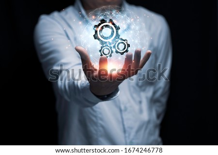 Businessman hand holding cog gear wheel infographic with sunlight. Engineering creative and business strategy concept. Royalty-Free Stock Photo #1674246778