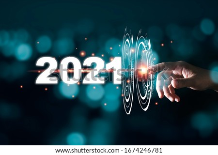 Hand touching pass thru infographic to 2021 year with blue bokeh and dark background. New year change concept. #1674246781