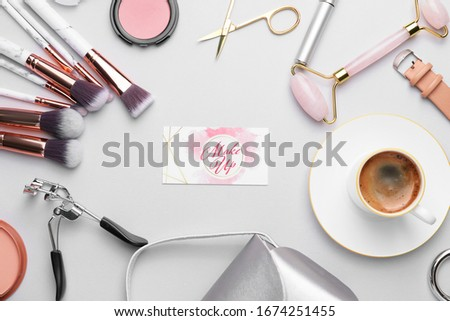 Decorative cosmetics and accessories with business card of makeup artist on white background