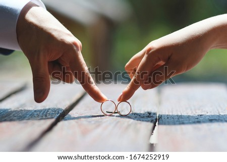 bride and groom plying with wedding rings on table #1674252919