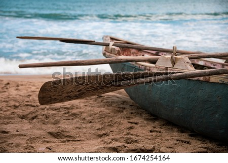Close up on the wooden oar of a fishing boat on the beach. Tropical Caribbean paradise. Dominican Republic typical seascape. Selective focus Royalty-Free Stock Photo #1674254164