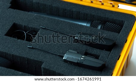 audio equipment lavalier microphone and wireless microphone. white backround in the yellow case
