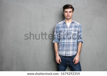 normal young man standing on a grey background concrete wall #1674292354