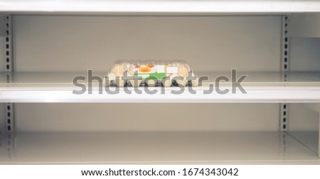 Covid-19 or Coronavirus and panic buying concept.Empty eggs shelves supermarket store.novel coronavirus covid-19 outbreak panic people.Food shelf has been wiped out from panic buying.panic shopping. Royalty-Free Stock Photo #1674343042