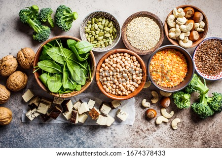 Vegan sources of protein background, top view. Tofu, chickpeas, lentils, nuts, spinach and broccoli are vegetable proteins.