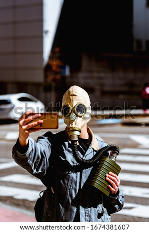 Person takes selfies with a gas mask during global epidemic. conceptual. global crisis.