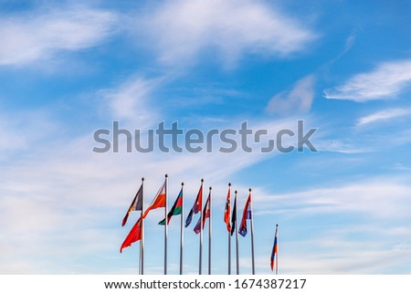 Flags of different countries on a flagpole against a blue sky. Natural photo.