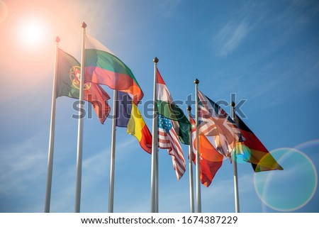 Flags of different countries on high flagpoles. Natural photo.