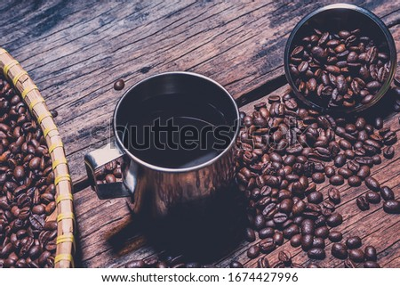 Traditional black coffee in big stainless steel cup and dark roasted coffee beans scattered on wood table in cinematic style picture.