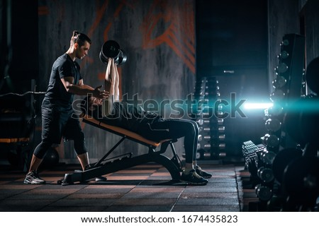 young man has workout with personal trainer in modern gym Royalty-Free Stock Photo #1674435823