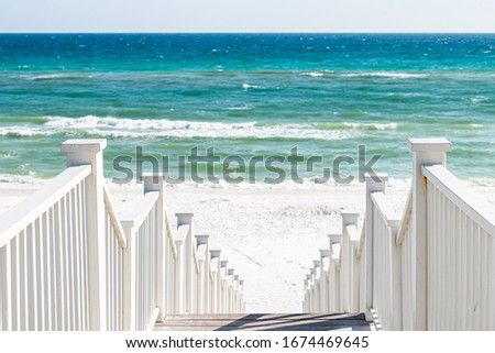 Seaside, Florida railing wooden stairway walkway steps architecture by beach ocean background view down during sunny day Royalty-Free Stock Photo #1674469645
